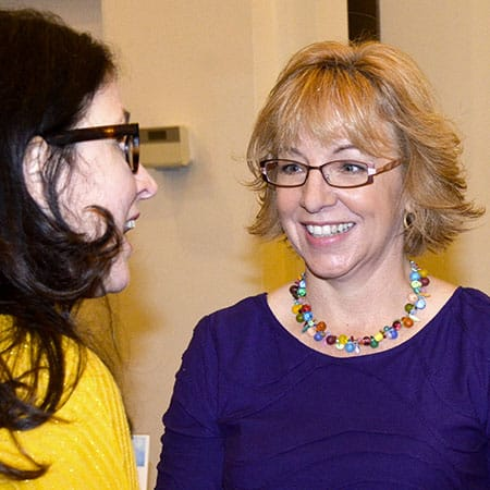 Melanie Davis speaking with individual